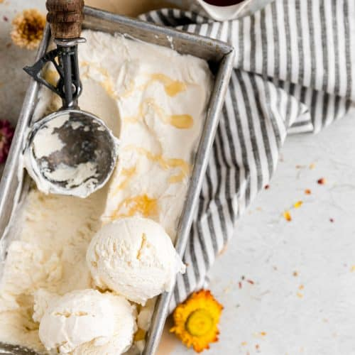 a tin filled with no churn honey vanilla ice cream. it has 2 scoops of ice cream piled on on side with an ice cream scooper sitting in the ice cream