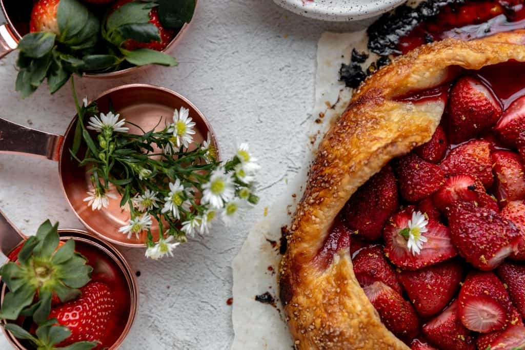 top view of a strawberry galette with copper measuring cups next to it that are filled with either strawberries or white daisies