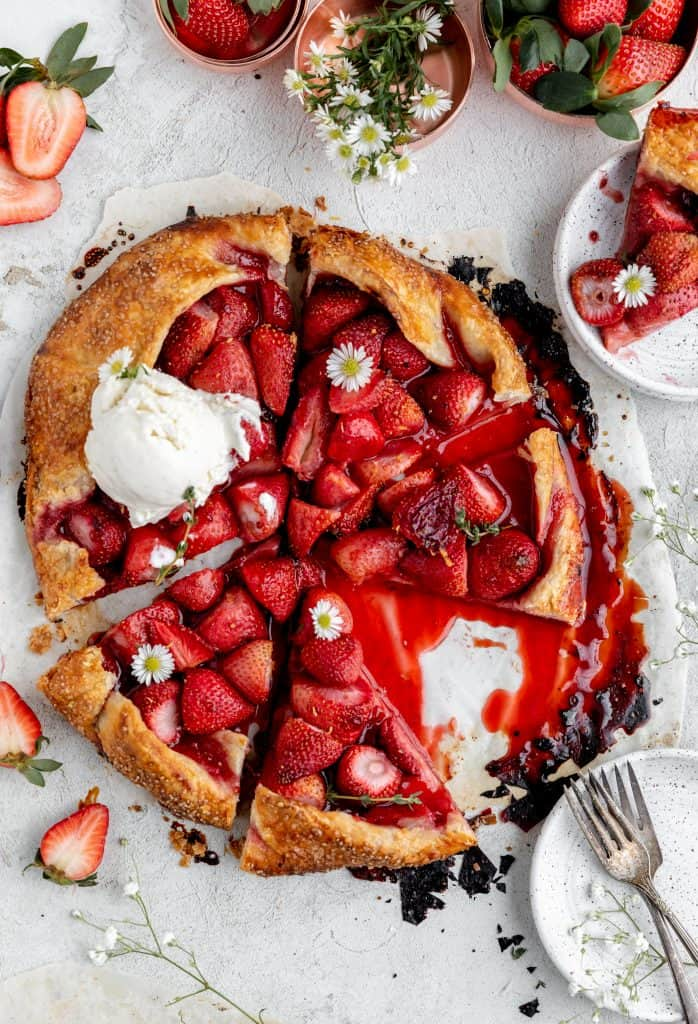 strawberry galette cut into triangles with one slice sitting on a white speckled plate and a scoop of honey vanilla ice cream on top of the whole tart garnished with white daisies