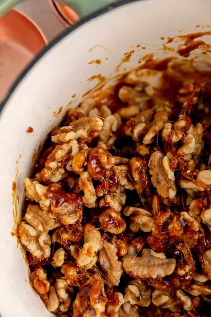 walnuts stirred up in a pan with the hot sugar all over them