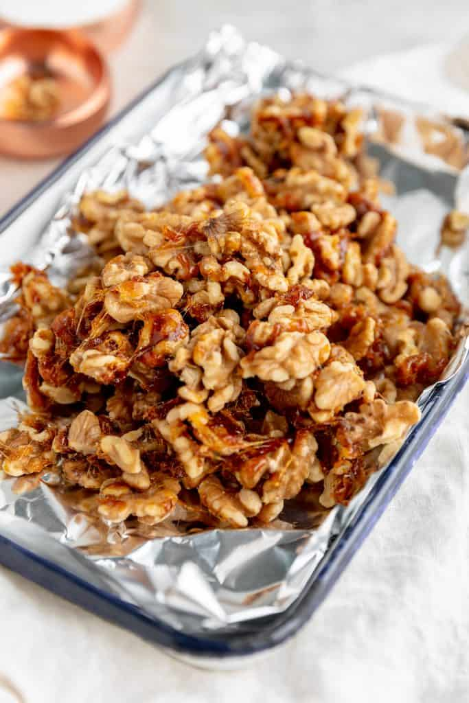 candied walnuts cooling on a pan lined with foil