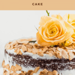 Close up of the whole almond carrot cake with yellow roses on top and toasted almonds on the outside of the cake
