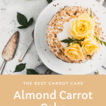 top view of the almond carrot cake on a white cake stand with toasted almonds on the outside of the cake and yellow roses on top. an antique pie server and rose leaves on the counter next to the cake