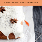 close up of an unsliced loaf of orange poppy seed bread topped with yogurt glaze, poppy seeds and star anise on top of white parchment paper on a dark wood surface with dried orange flowers