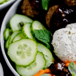 close up shot of the cucumbers, mint, garlic herb cheese spread, meatballs and fresh mint in the Mediterranean bowl