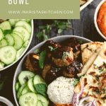 a bowl filled with Mediterranean meatballs, naan, garlic herb cheese spread, cherry pepper hummus, lemon chutney, cucumbers, red onions and fresh herbs