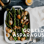 grilled asparagus in a white baking dish with glazed shallots and sherry vinaigrette sitting on top of a white linen on a dark surface