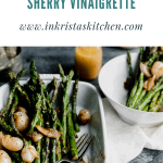 grilled asparagus in a white baking dish topped with glazed shallots and sherry vinaigrette sitting on a light colored linen on a dark surface with a plate full asparagus in the top right corner with vinaigrette next to it
