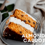 close up of almond carrot cake on a grey plate with a fork and a linen behind it