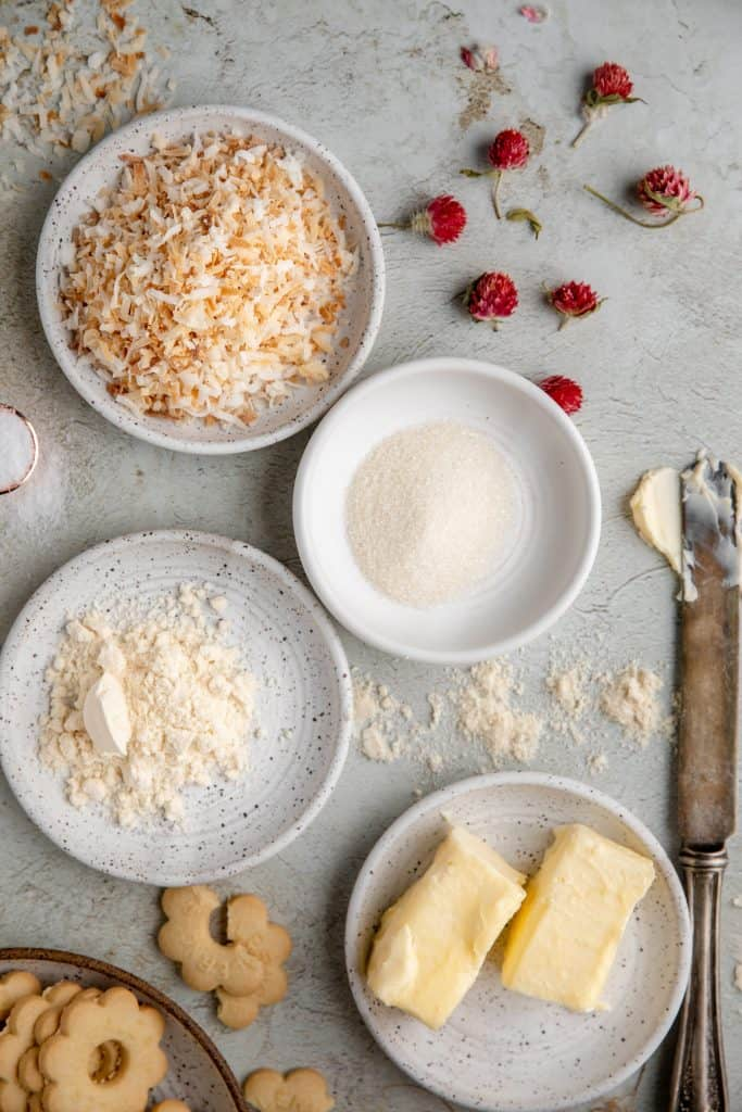 butter cookies, toasted coconut, sugar, butter, coconut flour and pink dried flowers all sitting in separate dishes
