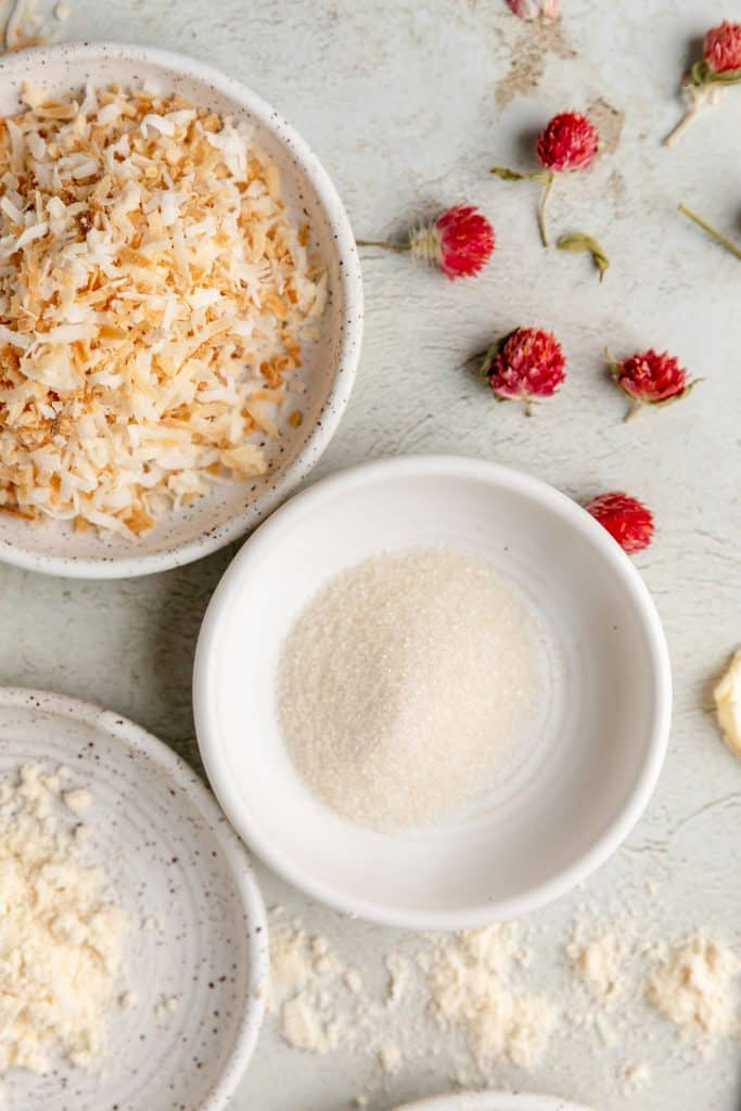 toasted coconut flakes, sugar in the raw and coconut flour measured out for the cookie crust with dried pink flowers