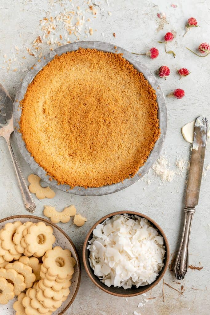 butter cookie crust baked to a golden brown with a dish of coconut flakes and butter cookies to the side