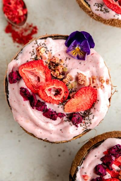 strawberry banana smoothie bowl served inside a coconut shell topped with freeze dried strawberries