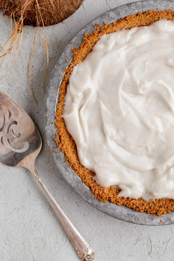 coconut cream filling in a butter cookie crust with a pie server to the side