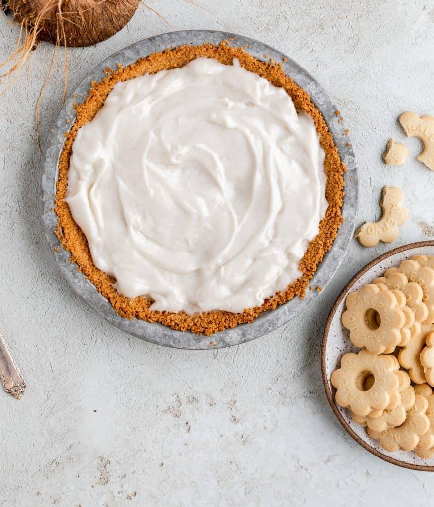 coconut cream pie before the whipped topping is added with a plate of cookies to the side