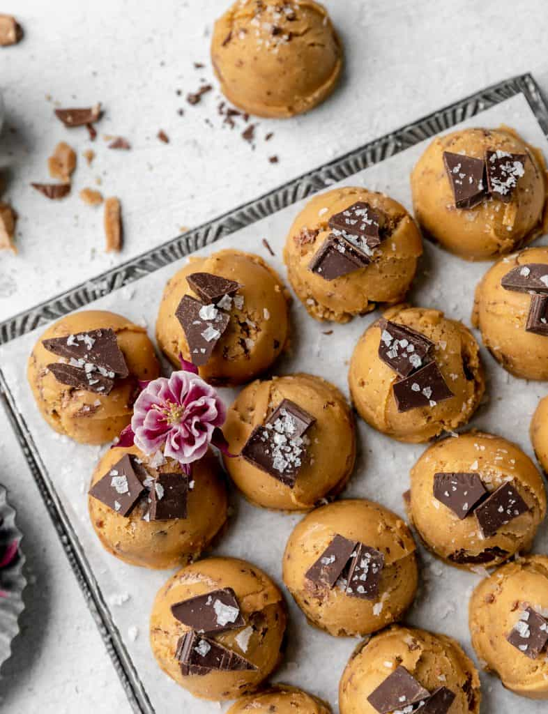 brown butter toffee chocolate chip cookies lined up on a sheet tray with flaky sea salt and a purple flower on top