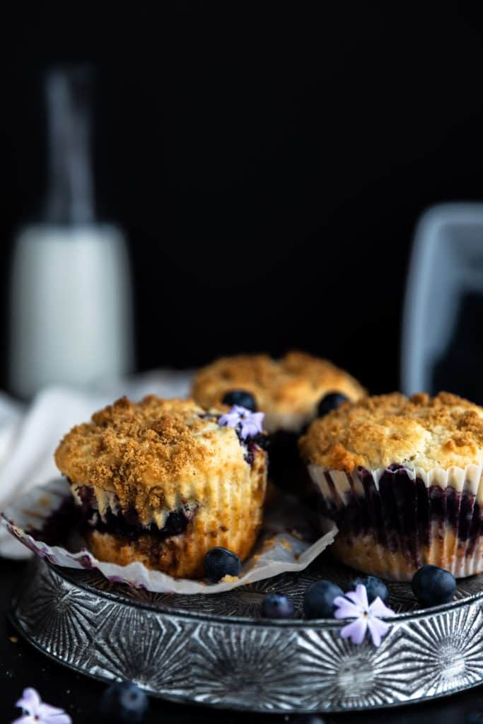 blueberry muffins with milk in the background