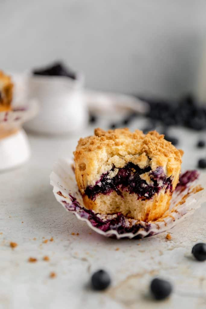 a blueberry streusel muffin with a bite taken out of it