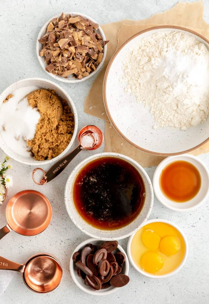 bowls of flour, brown sugar, granulated sugar, brown butter, salt, baking soda, vanilla, eggs, chocolate and toffee pieces