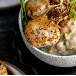 close up of scallops on top of a bowl of risotto with asparagus and peas