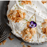 close up of a whole coconut cream pie with one slice cut out