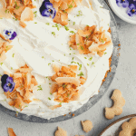 coconut cream pie with toasted coconut flakes, butter cookies and purple johnny jump up flowers