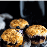 3 blueberry streusel muffins with one of the wrappers pulled down