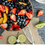 peaches, strawberries, blueberries and blackberries in a bowl for summer fruit salad with lime ginger dressing