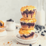 a stack of 3 blueberry streusel muffins on a small plate
