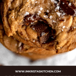 brown butter toffee chocolate chip cookies stacked up with a bite out of the top one