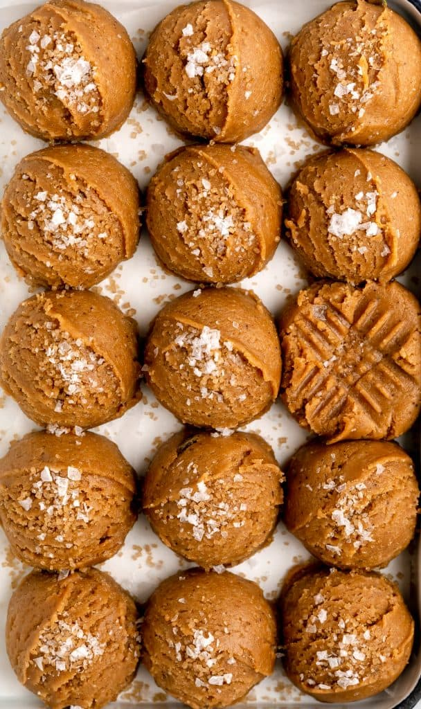 raw peanut butter cookie dough scooped into 2oz balls and topped with demerara sugar and flaky sea salt