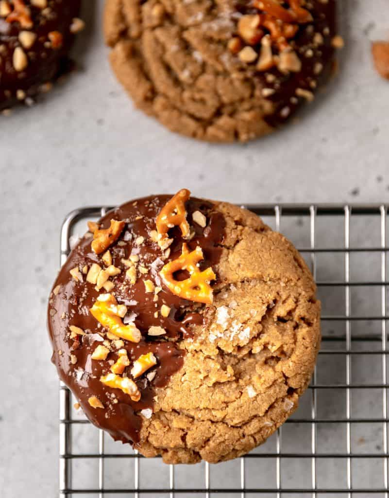 a peanut butter cookie dipped in chocolate sitting on a cooling rack