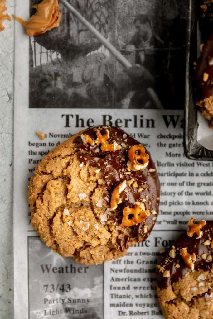 peanut butter cookies dipped in chocolate set on a newspaper deli sheet