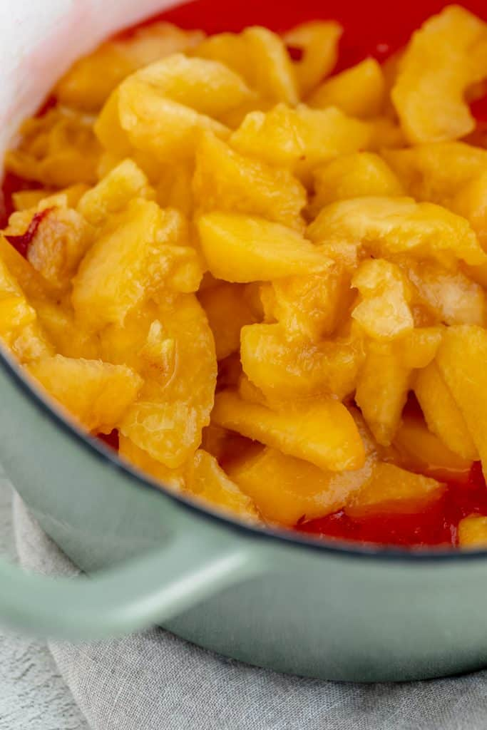 fresh cut peaches being mixed into the Jello mixture