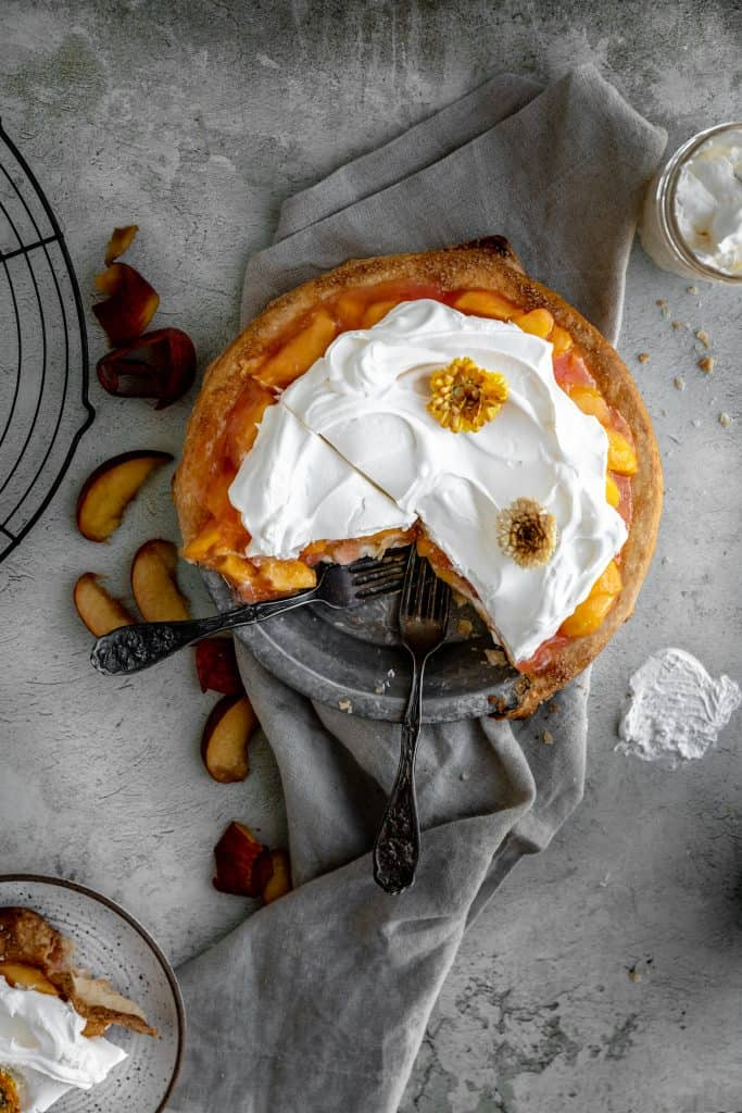 peaches and cream pie with a couple slices cut out of it and 2 forks in the pan
