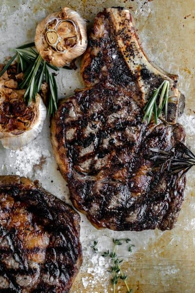 grilled steaks on a tray with roasted garlic heads