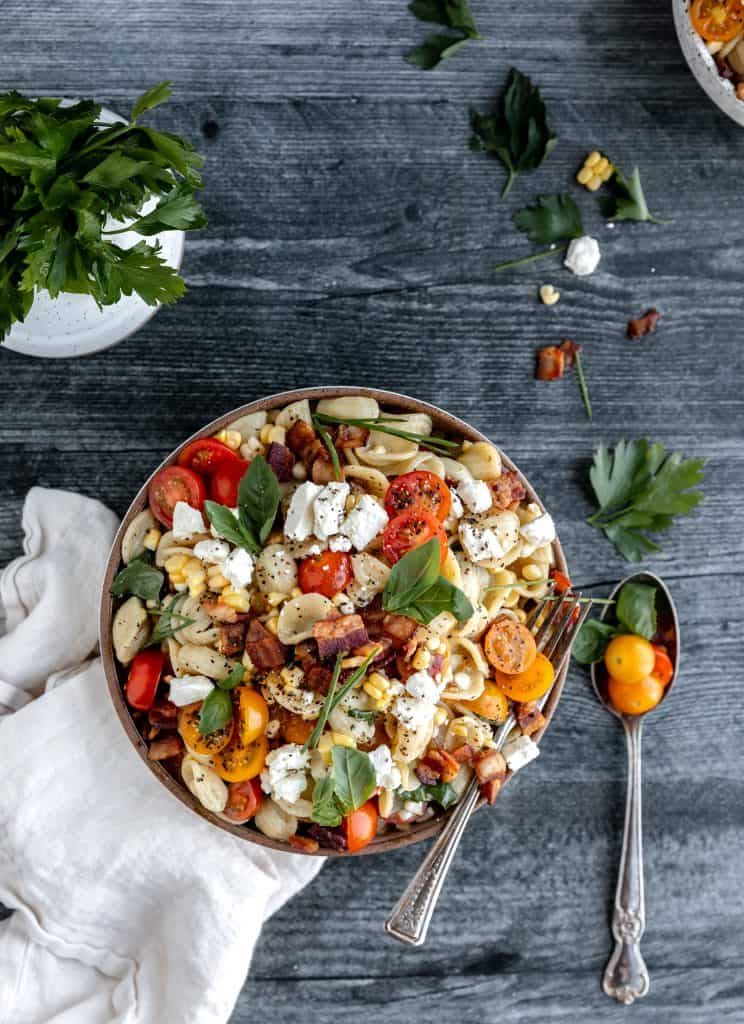 summer pasta salad with linen and a spoon next to the bowl