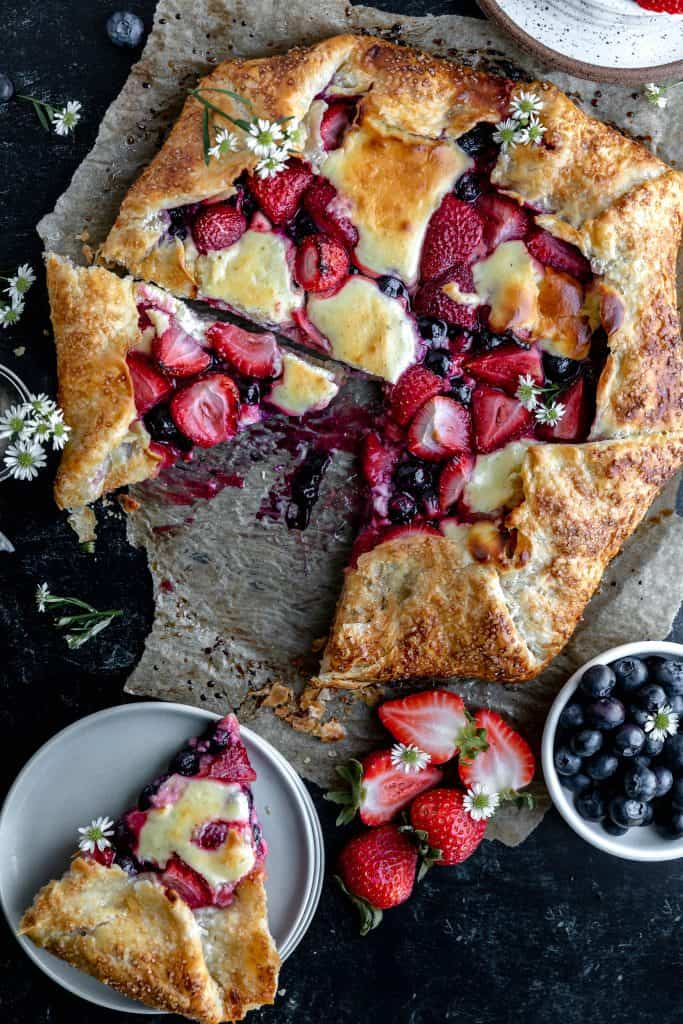 berry cheesecake galette with a slice cut out and set on a stack of plates