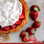 strawberry cream cheese pie topped with cool whip and white flowers