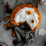 peaches and cream pie with 2 slices taken out and forks inside the pie dish