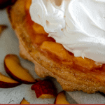 close up of peaches and cream pie with an overhanging crust