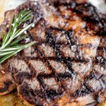 Bone in Ribeye close up with grill marks, flaky salt and rosemary