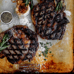 2 grilled bone in ribeyes with rosemary and roasted garlic