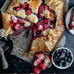 overhead view of a berry cheesecake galette with a slice cut out of it