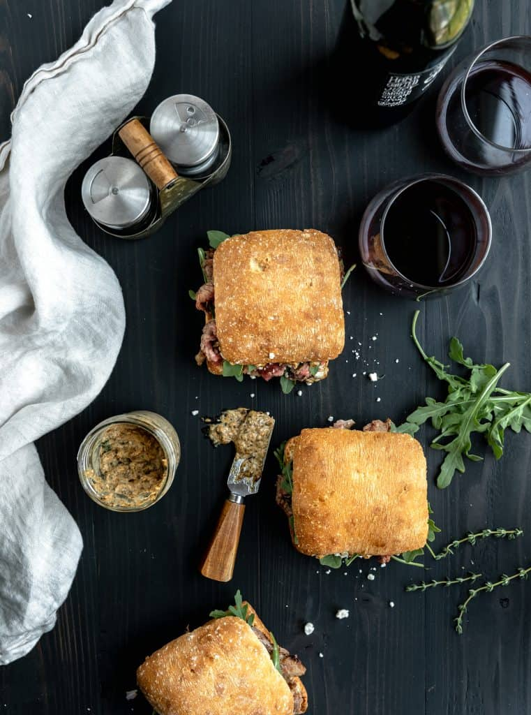 a spread of steak sandwiches, burnt onion aioli, red wine and a linen cloth laid out on a black table