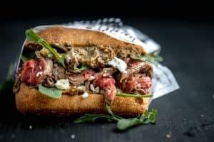 marinated flank steak sandwich on ciabatta with arugula and blue cheese