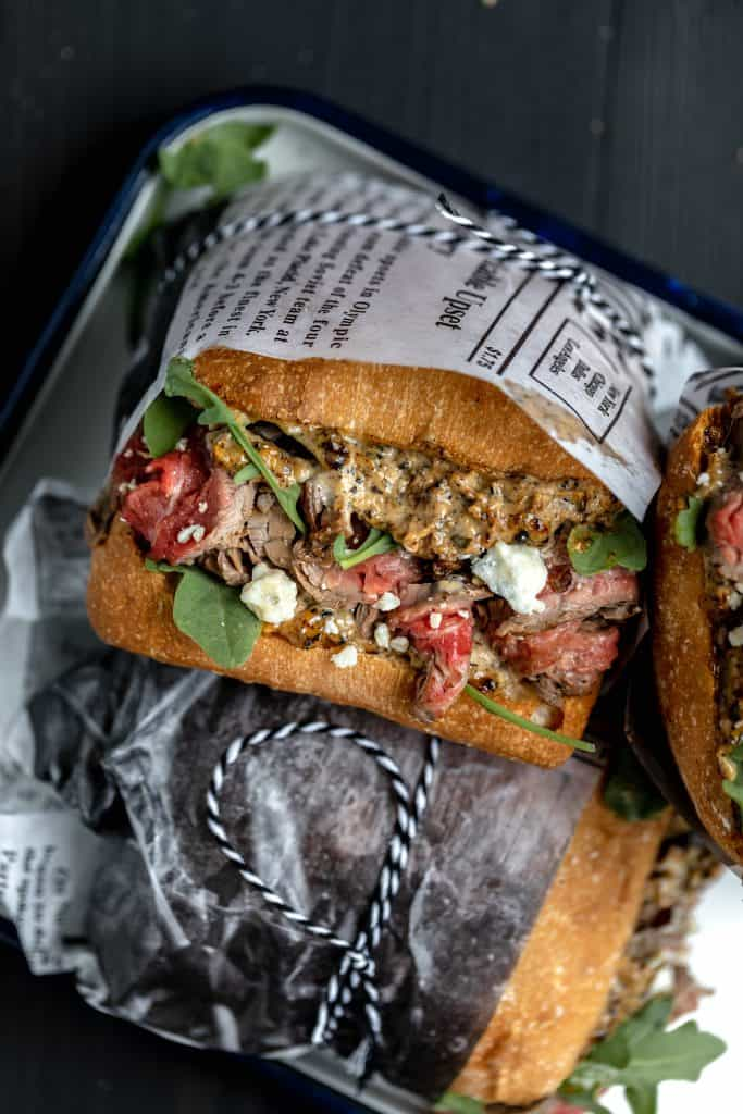 steak sandwich on ciabatta with arugula and blue cheese wrapped in deli paper