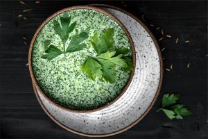 creamy schug sauce in a bowl topped with parsley