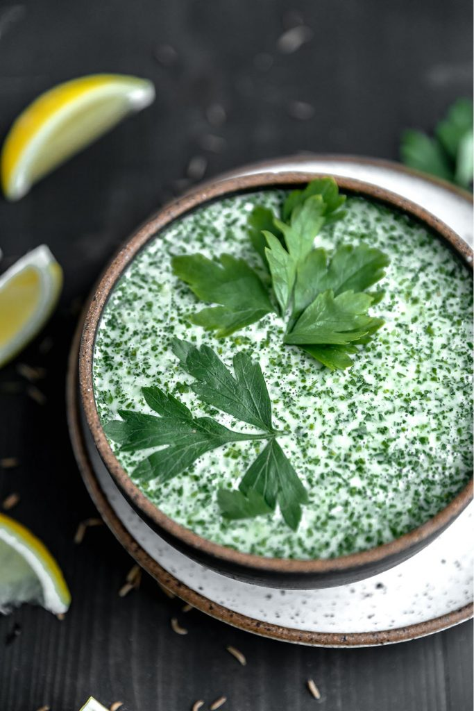 a bowl of creamy coconut schug sauce with parsley on top and lemons on the side