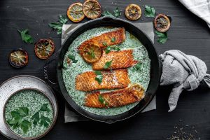 a skillet with salmon, sauce and microgreens